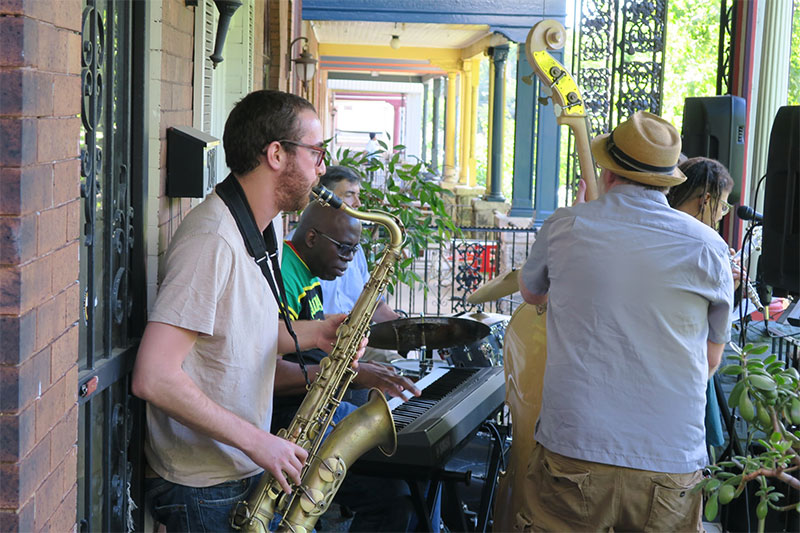 A group of musicians play on a porch