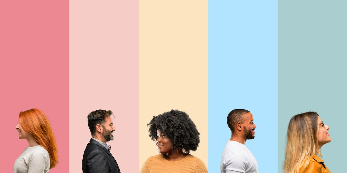 A diverse group of 5 people, each standing in front of a different color.