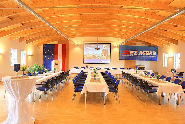 Image of banquet hall with a beamer at the front and a big EZ Agrar Logo
