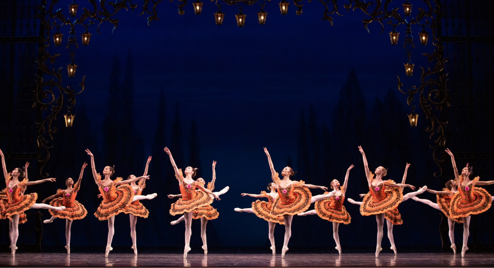 Chorus of ballerinas in bright orange tutus dance on point under lanterned archway and night sky.