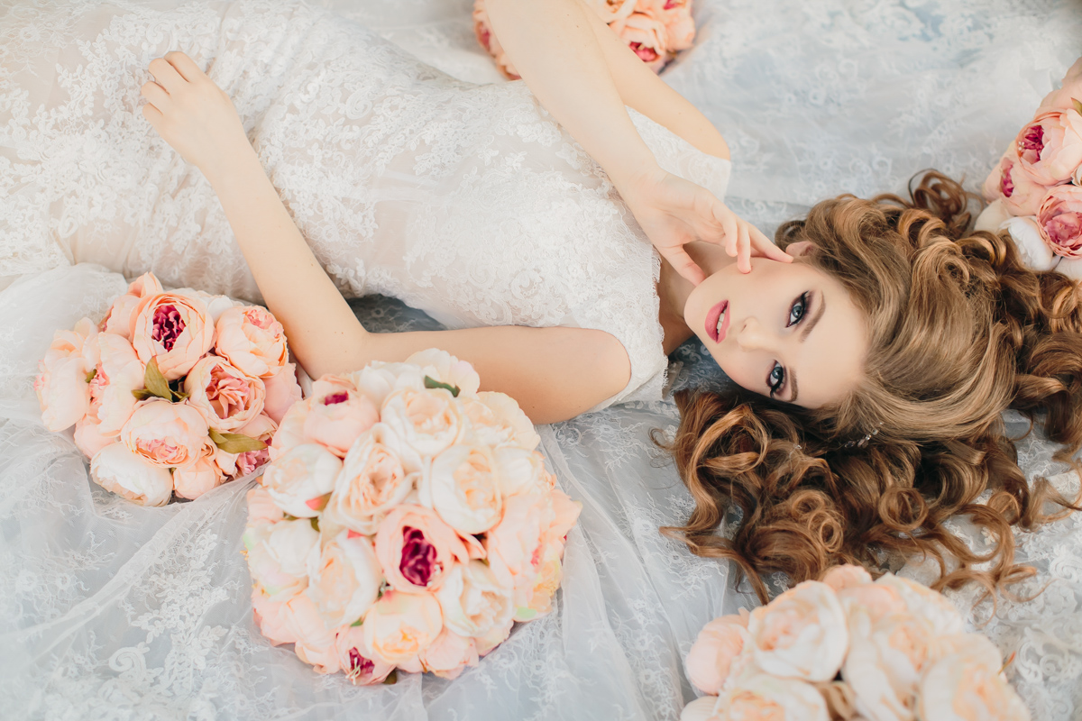 A redhead bride laying down with the pink flowers