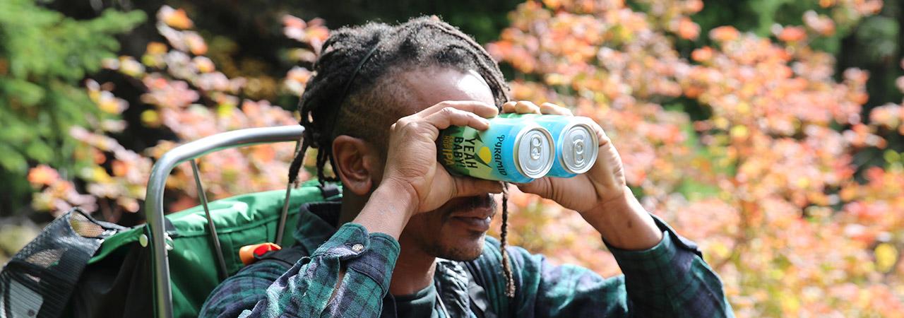 Dude using Yeah Baby! cans like binoculars
