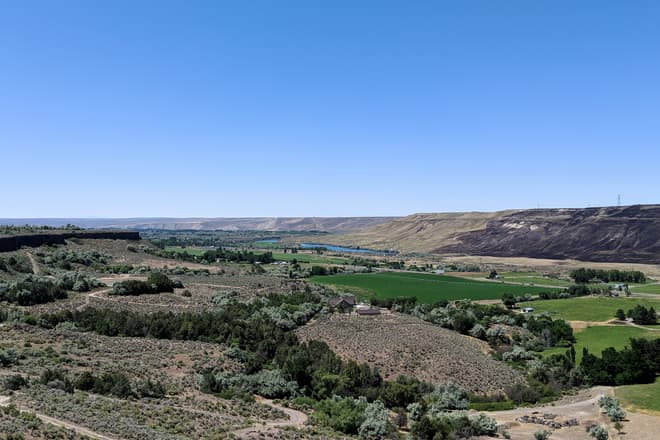 A low, wide desert river valley. Regular bright green farm fields punctuate the much less vibrant desert scrubland.
