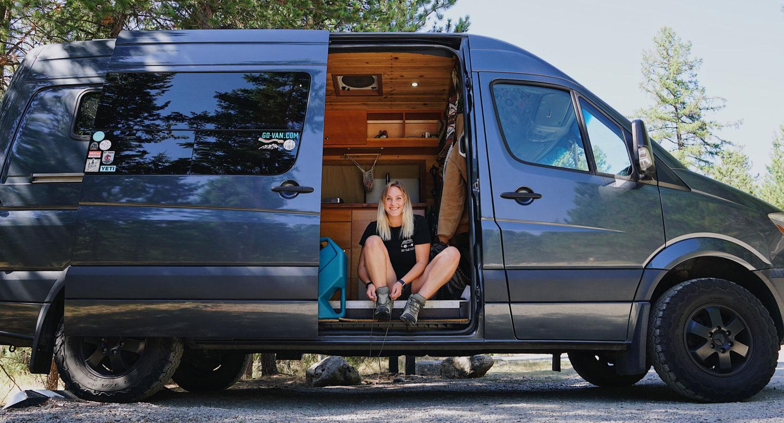 Van Life Katie Larson putting on hiking boots in her van at a primitive campsite