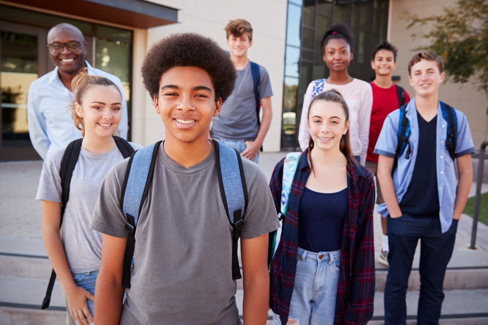 Diverse group of students pose in a group in front of their school building.