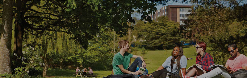Students sitting outside laughing on the University of Birmingham campus