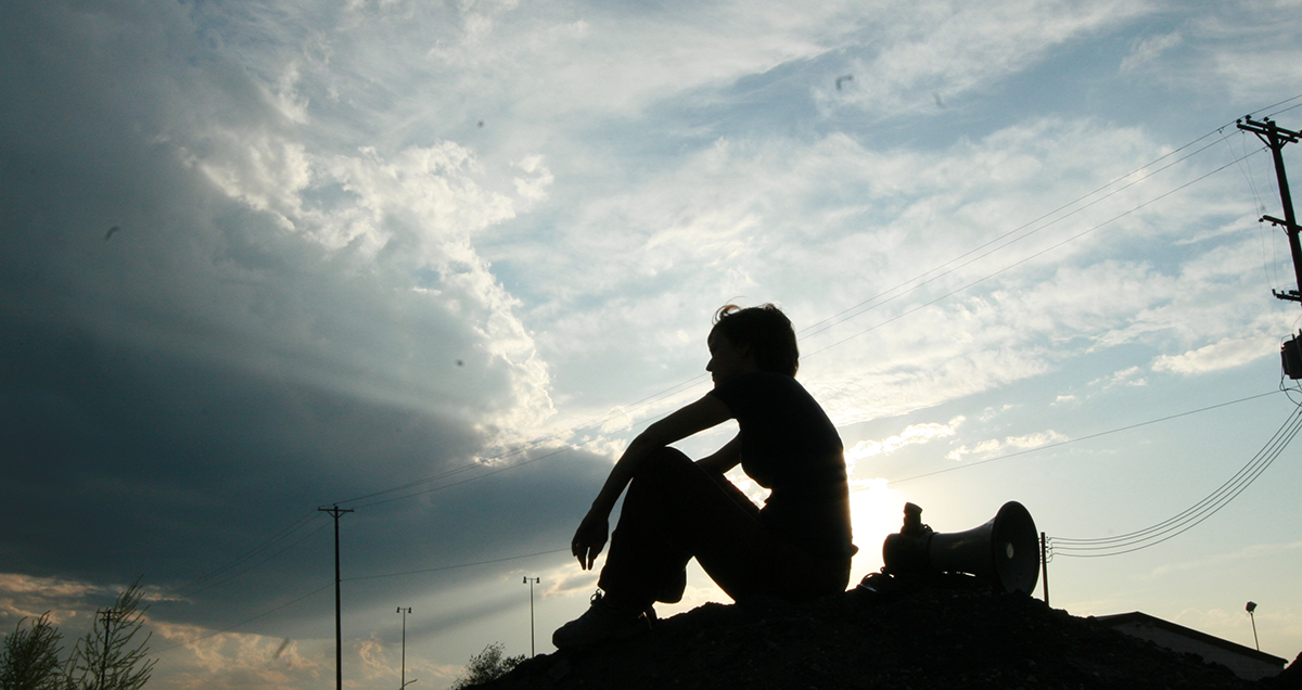 Silhouette sitting on a hill, beside a bullhorn