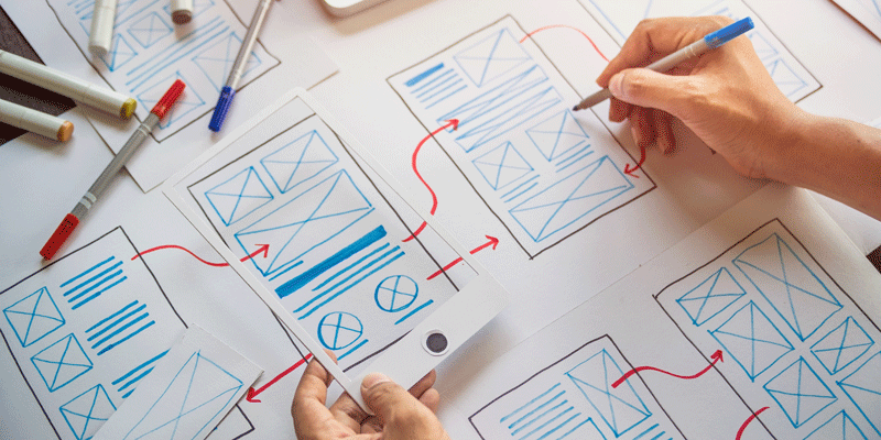 A UX designer drawing some wireframes on a sketchpad