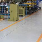 Carrelli e macchinari disposti su un pavimento in resina munito di segnaletica orizzontale.