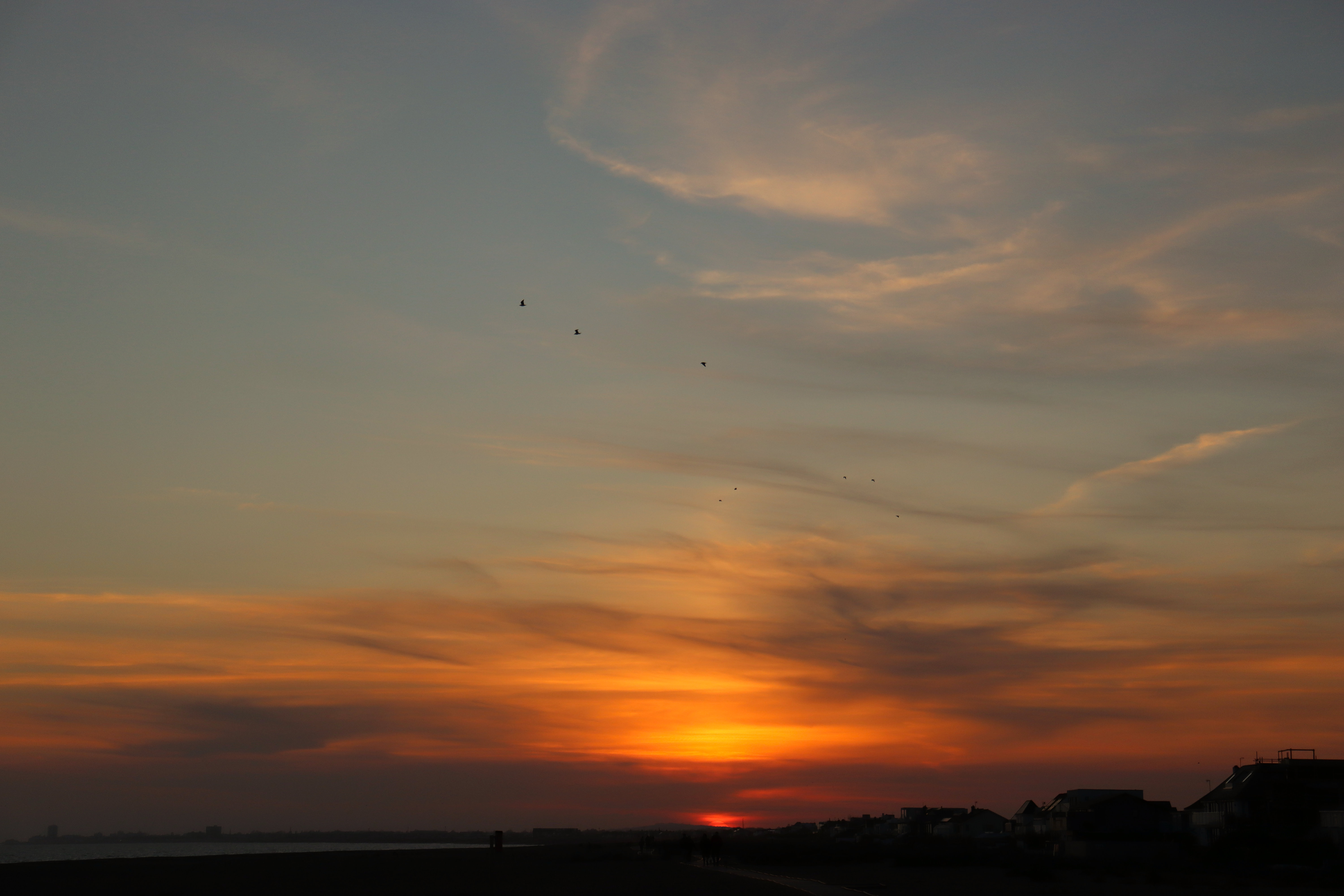 Shoreham beach with a red sunset in the distance and some birds flying between the wavy clouds.