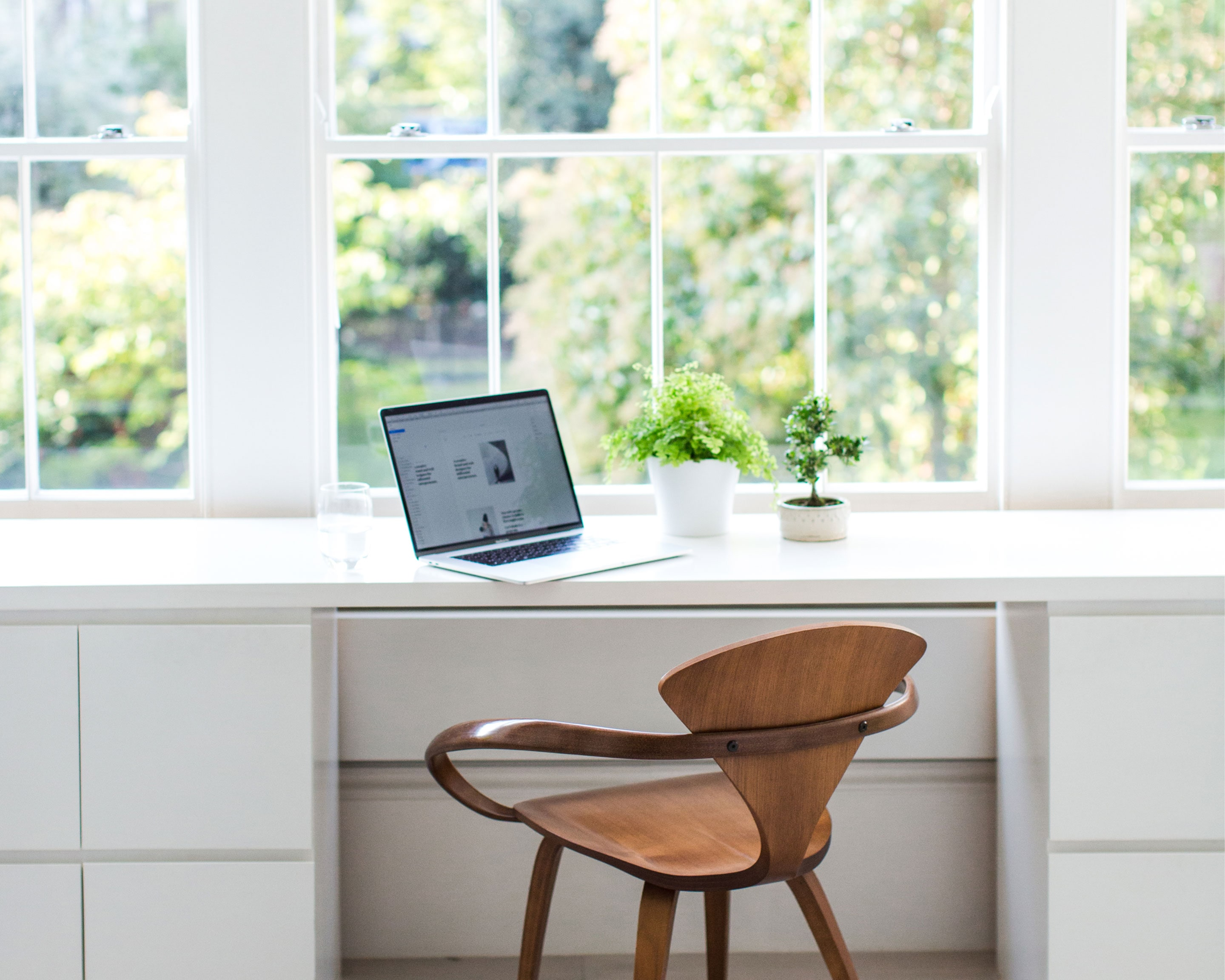 Jack Watkins light filled, bright white office space and desk with minimal styling, plants and MacBook