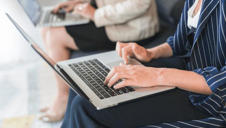 Entrepreneur business person working on laptop, using technology, next to a colleague on a shiny black desk #entrepreneur