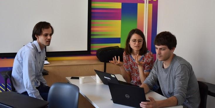 Deux hommes et une femme sont assis autour d'une table avec deux ordinateurs. Ils discutent et échangent.