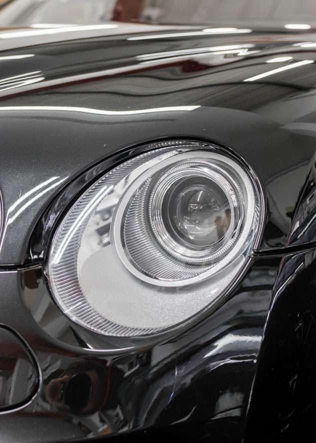 Close up shot of one Bentley Flying Spur car headlight with fog/cloudiness removed after headlight restoration