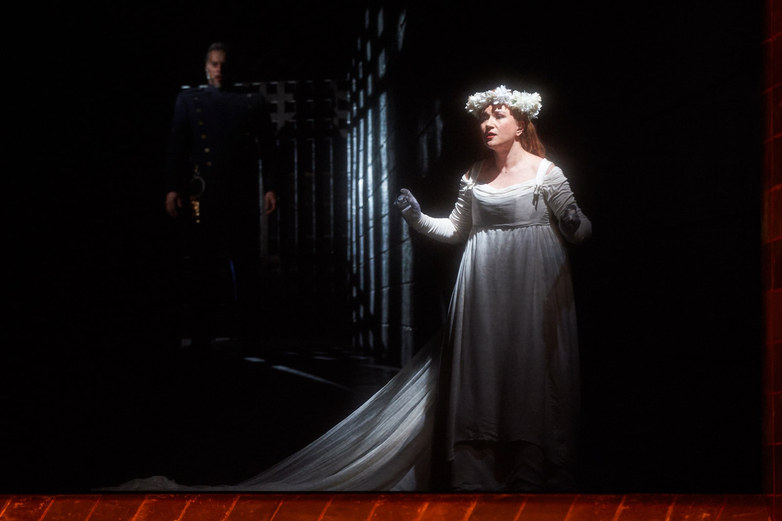 Bride with floral crown stands spot lit in darkened room with man looming in shadows of gate behind.