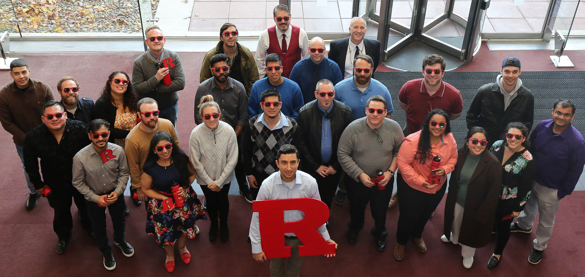 Rutgers boot camp students holding the letter R