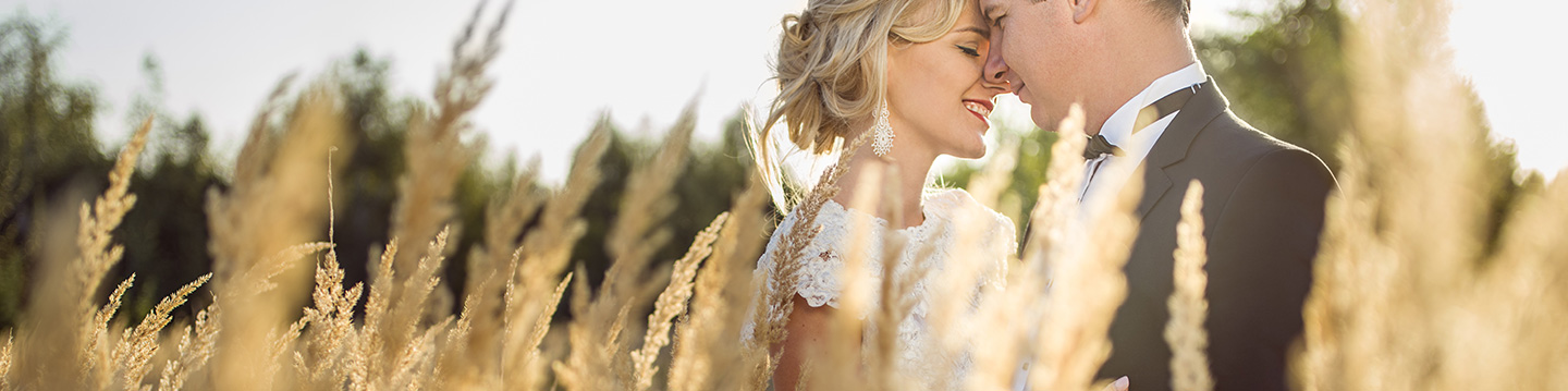 Bride and Groom posing in a field
