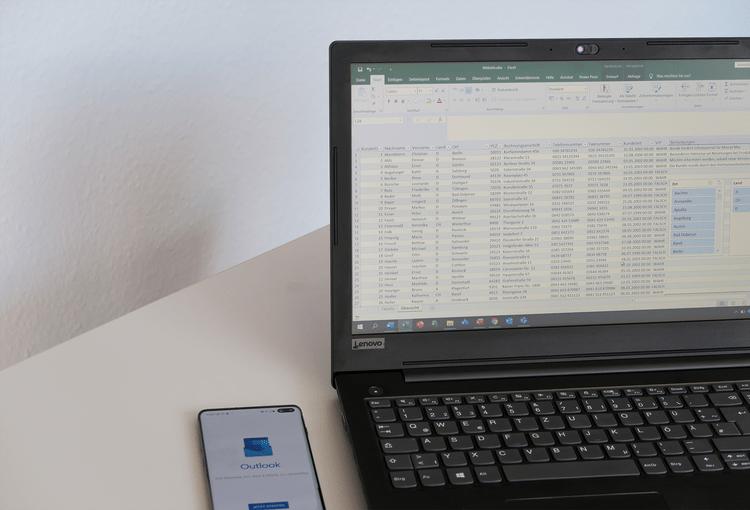 Smartphone mit Outlook-App neben einem Laptop