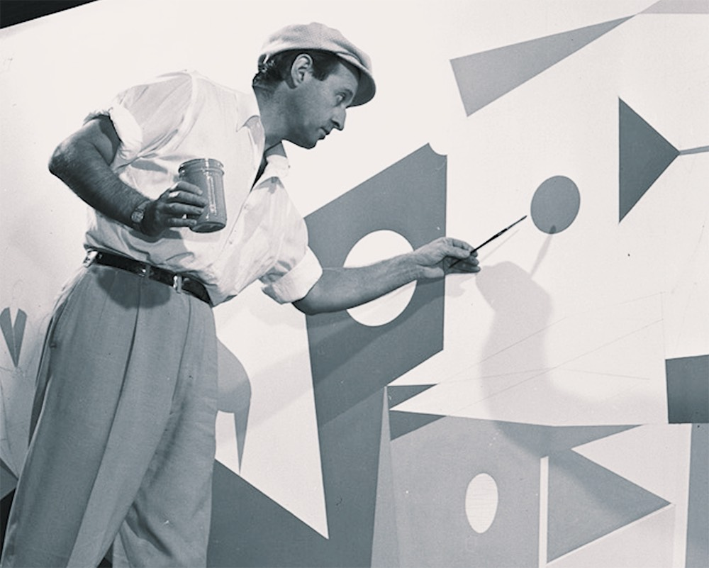 A black-and-white photograph of Lester Schwartz painting.