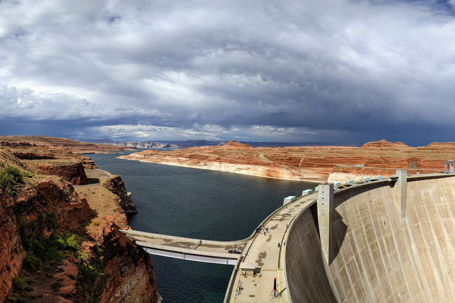 The Glen Canyon Dam, with Lake Powell extending behind it to the horizon. The rocks on either side of the lake are bright red-orange, but turn white just above the water. A thunder storm can be seen in the distance.