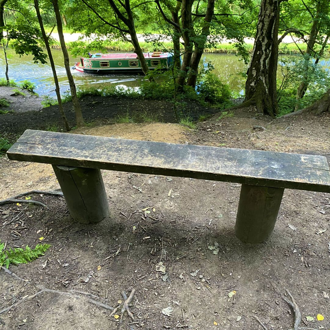 Bramley Fall Woods bench overlooking canal with canal boat