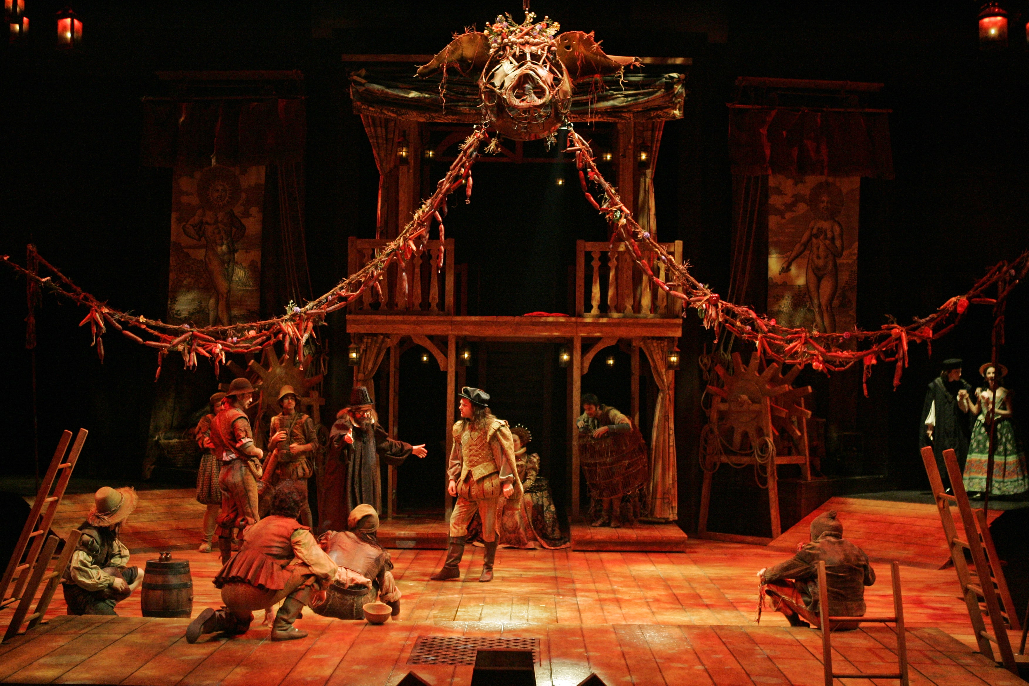 Company of theatrical players carouse under canopy of decorative pig and sausage garlands, bathed in red light.