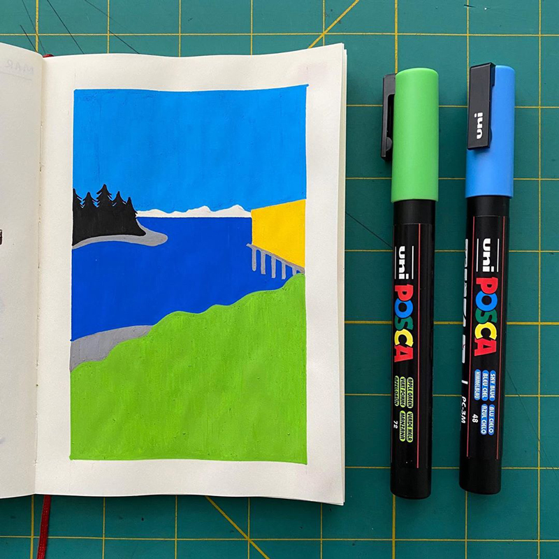 A blank notebook with a paint pen drawing of a bay with mountains behind it. A green and a blue pen are laid next to the notebook.