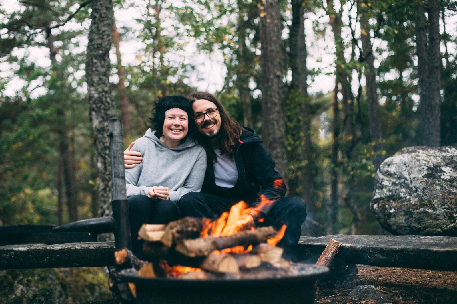 A smiling couple in a forest. Resting on a log close to a campfire.