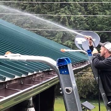 man spraying gutters