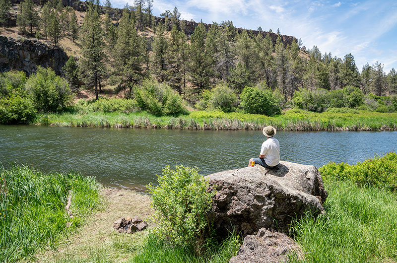 A man sitting on a large rock on the edge of the Deschutes River looking at the river