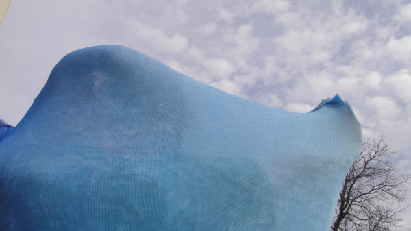 A body sock made of hombre-faded sky blue lycra. The wearer can perform it outdoors, blending into the skyscape behind her.