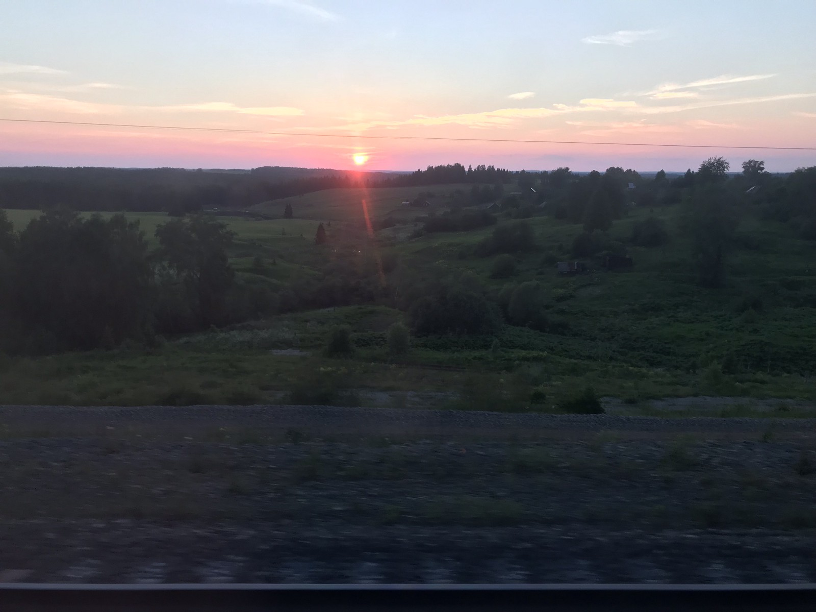 A sunset over hills of Russia, seen through the train's thick windows.