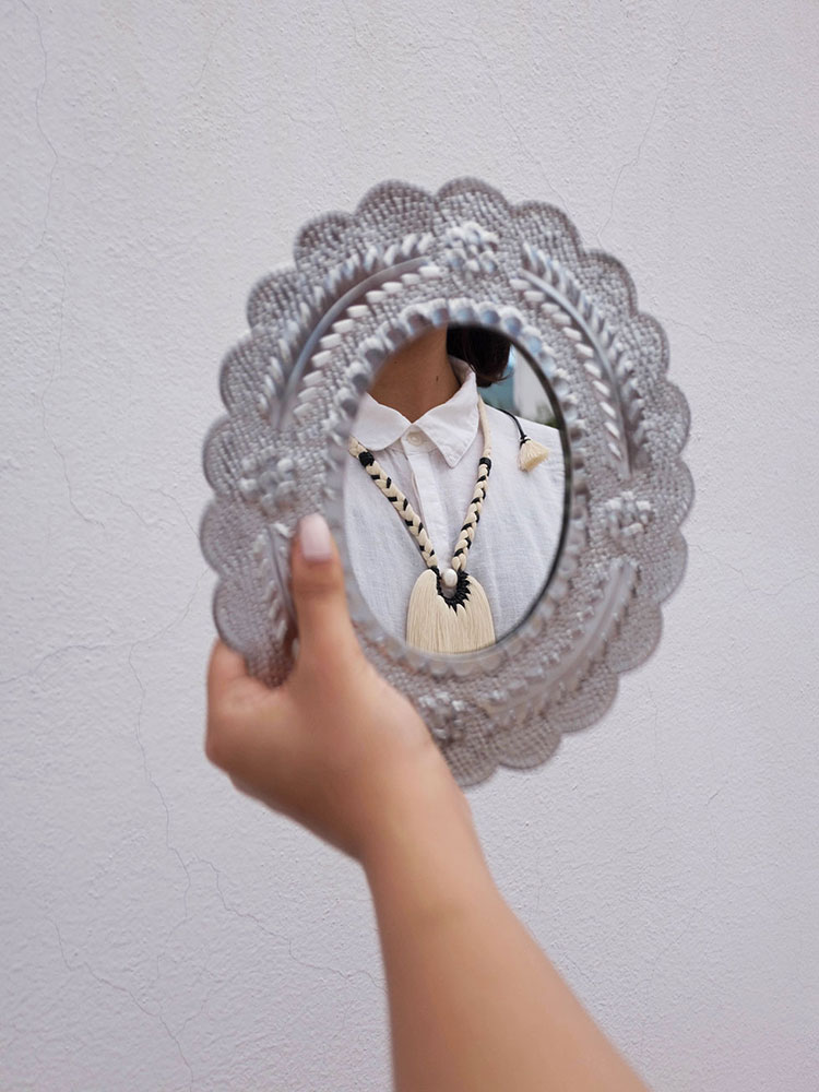 Hand holding tin mirror with reflection of necklace