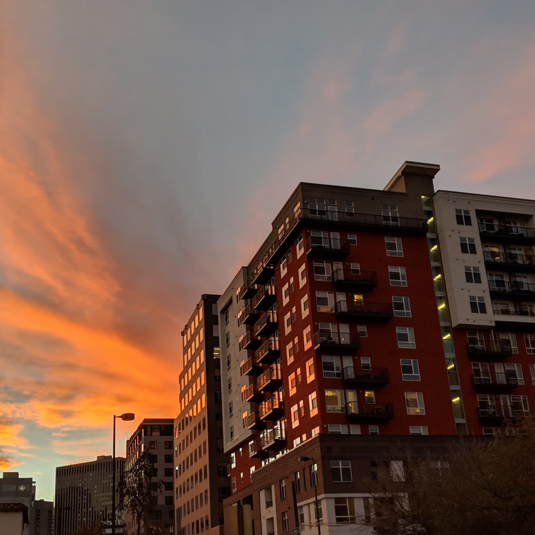 A row of apartment buildings at sunset. The nearest apartment block has maroon-colored sides that compliment the bright orange of the clouds above.