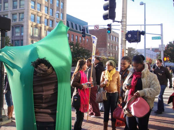 A woman in Central Square dons the green fabric envelope, while her friends look on.