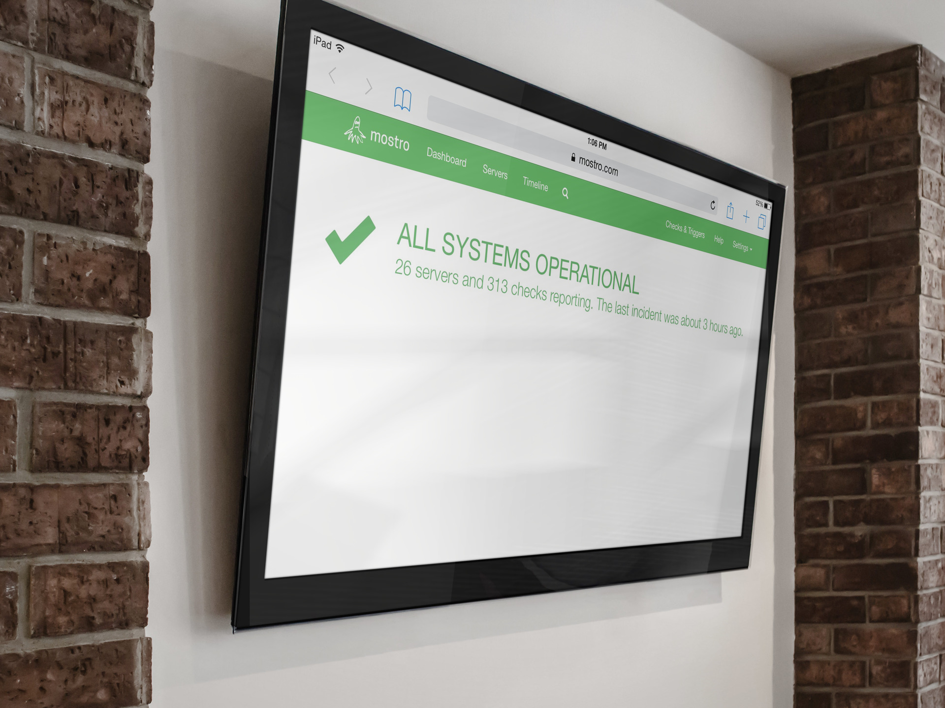 TV mounted on a wall displaying the Mostro dashboard with a green navbar and a green checkmark with the text: 'All systems operational. 26 servers and 313 checks reporting. The last incident was about 3 hours ago.'