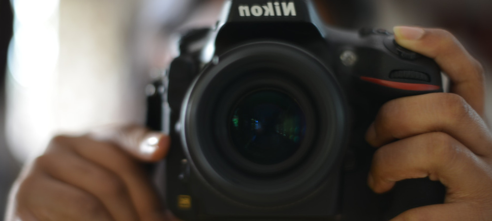 A nikon camera in center frame pointing at the camera