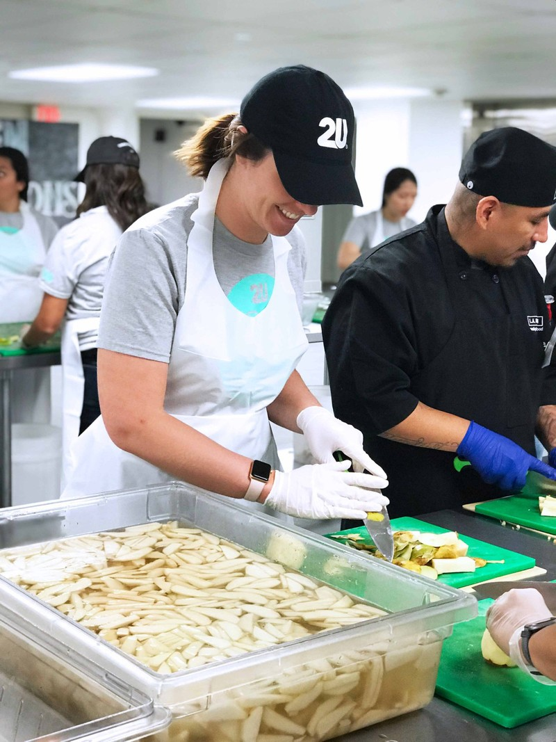 A 2U volunteer cuts potatoes in a kitchen with others on their day of service