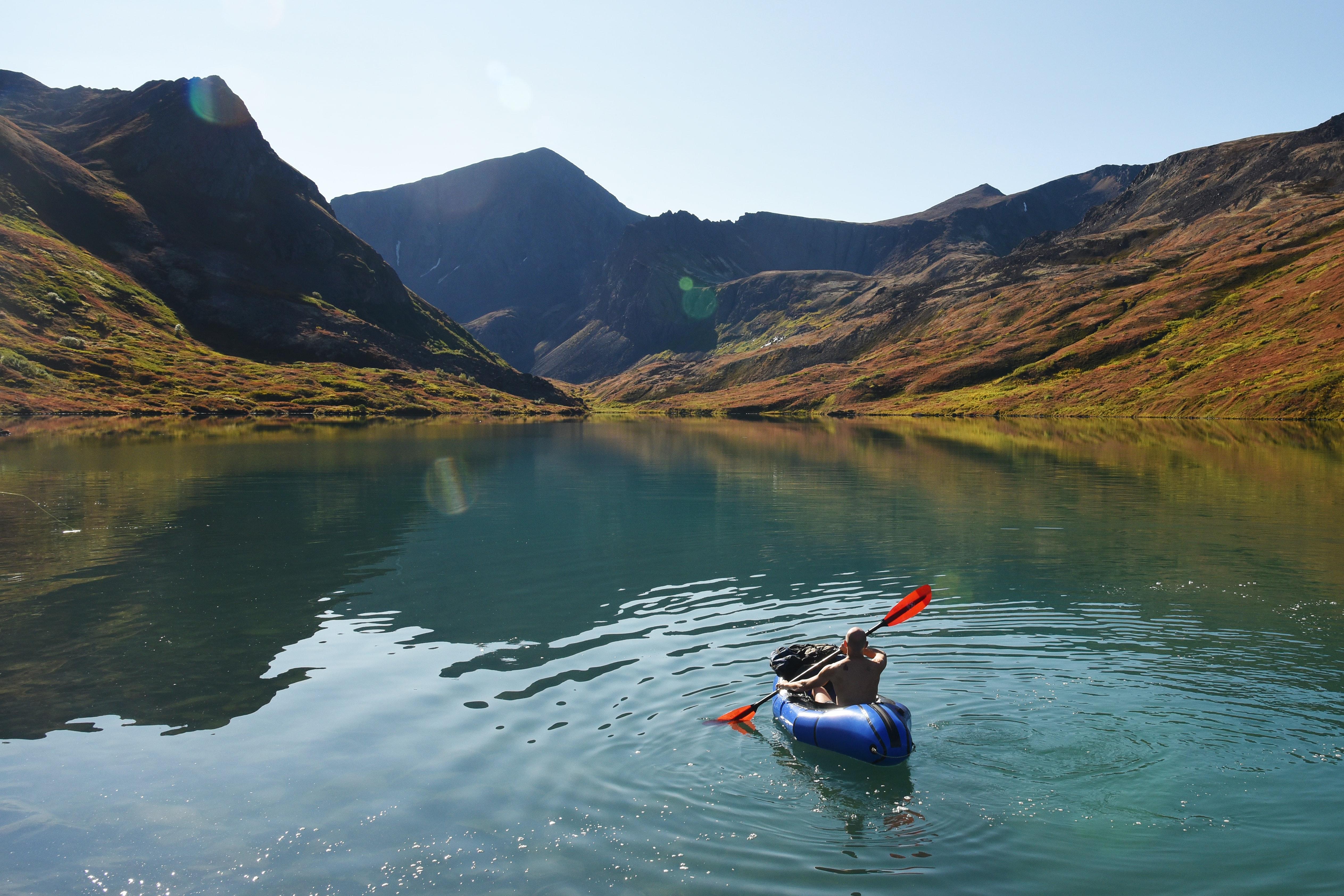 kayaker paddling on a lake in chugach state park in alaska