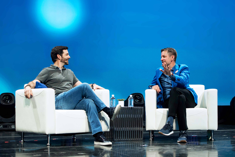 2U CEO and Co-Founder Chip Paucek speaks onstage sitting in white chairs