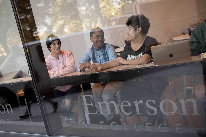 Students at Emerson College socialize next to a window in an academic building