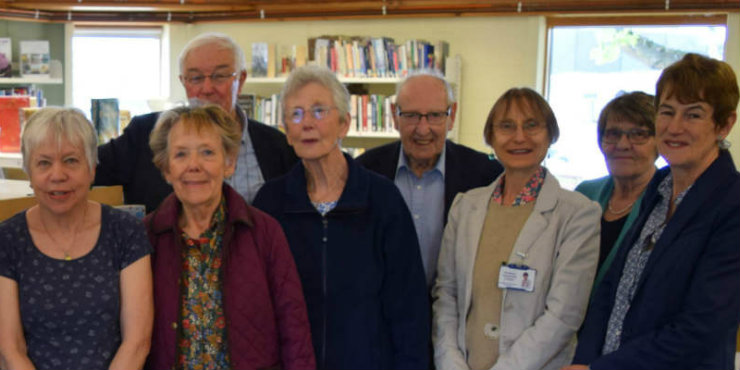 8 people posing for a photo in a small library.