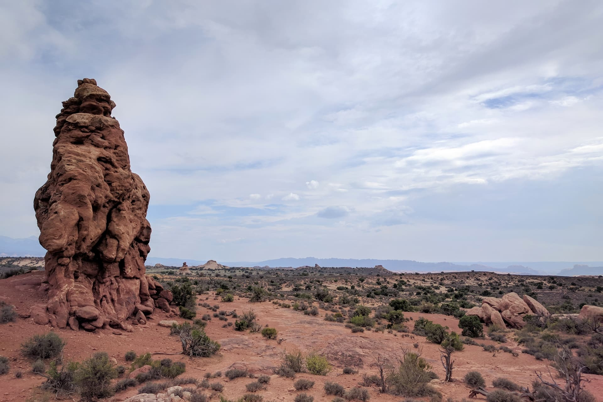 A lone pillar of red sandstone emerges from the desert ground in Arches National Park.