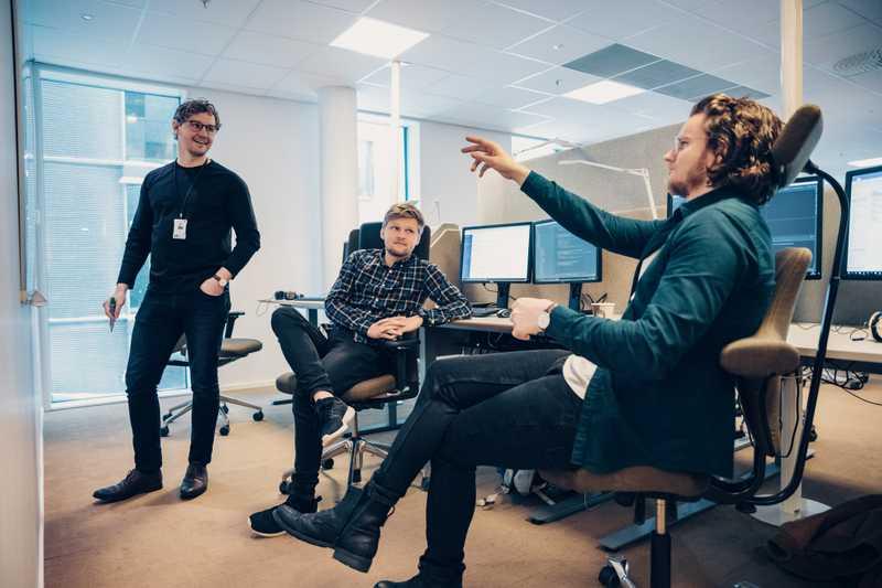 Tre lyshudede menn. En står og to sitterr på kontorstoler. En av dem som sitter peker på en whiteboard som er foran mennene.