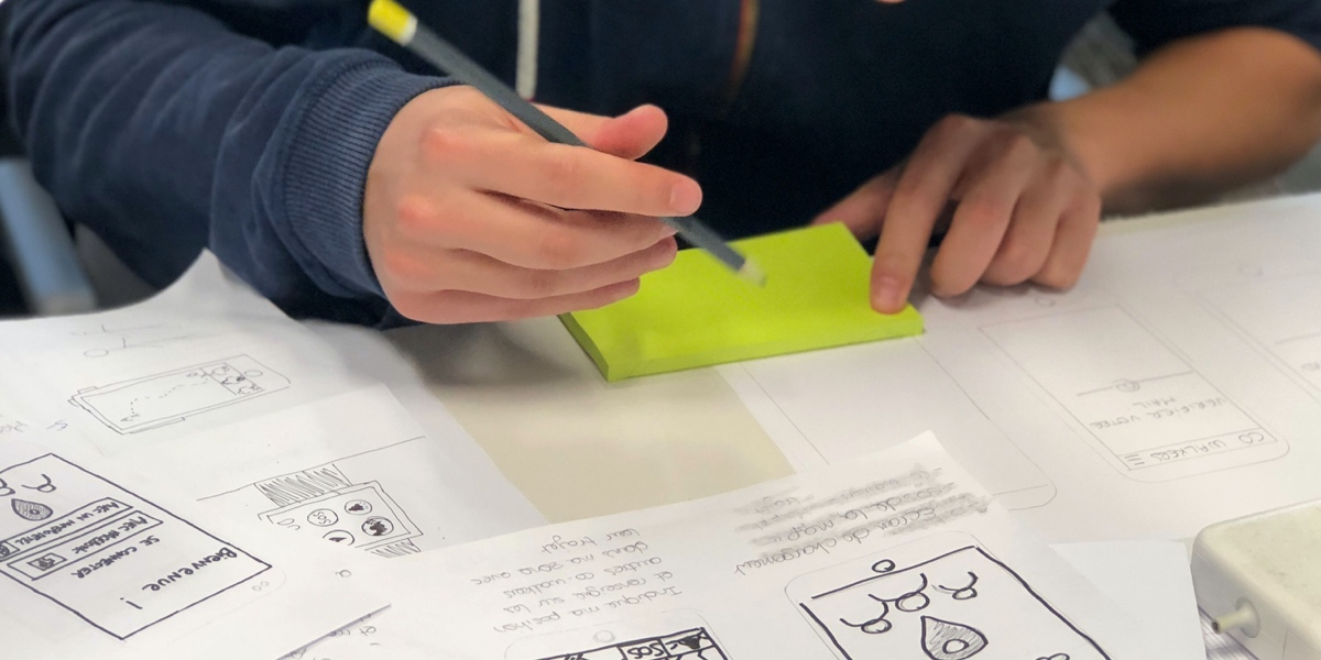Close up of a UX writer's hands, creating paper prototypes for an app