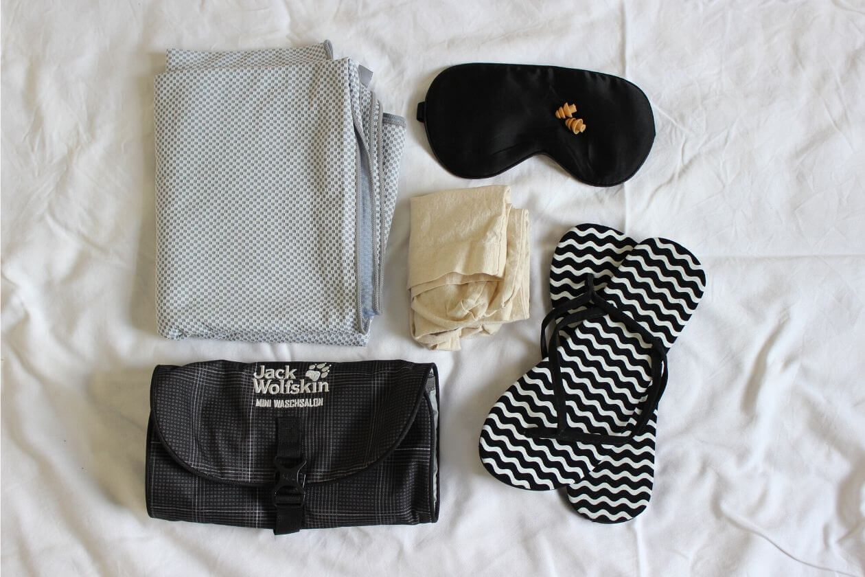 Reisehandtuch, Kosmetikbeutel mit Haken, Badeschlappen, eine Tüte für Klamotten, Schlafmaske und Ohrstöpsel