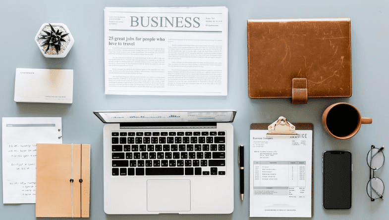 Laptop, notebook, folder, clipboard, plant, glasses, case, documents, newspaper on blue desk #accounting