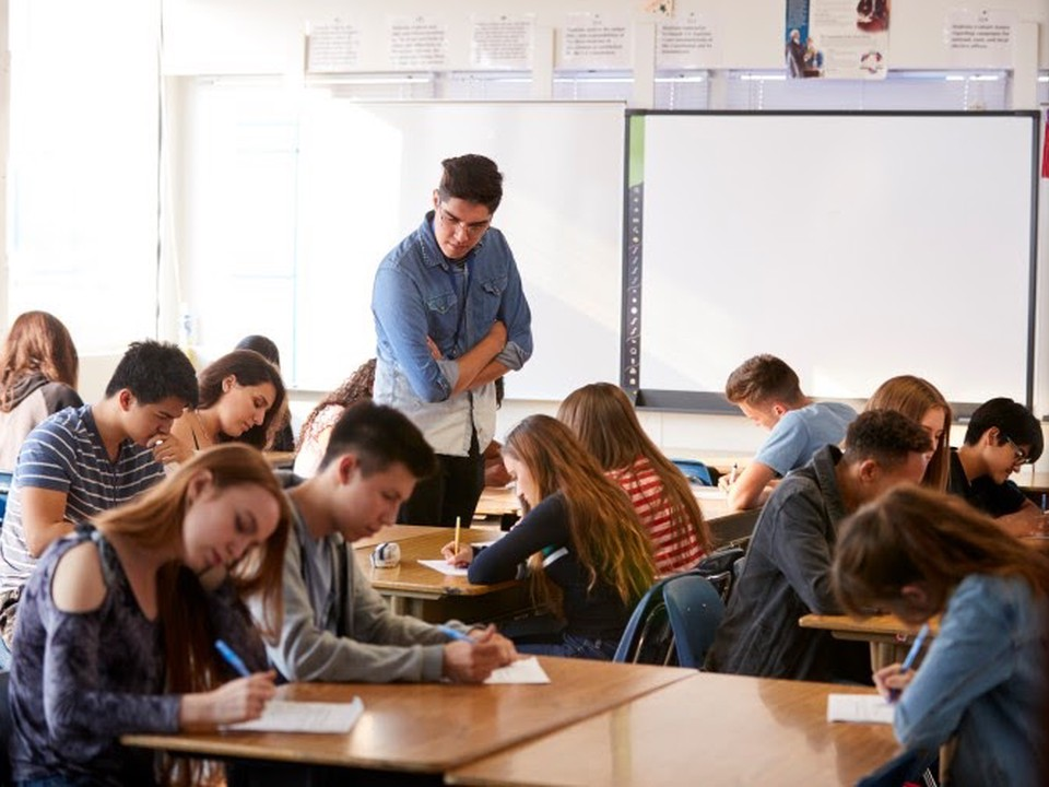 A high school stands among students working at their desks.