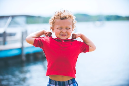 Kid flexing his arms, showing off his cannons