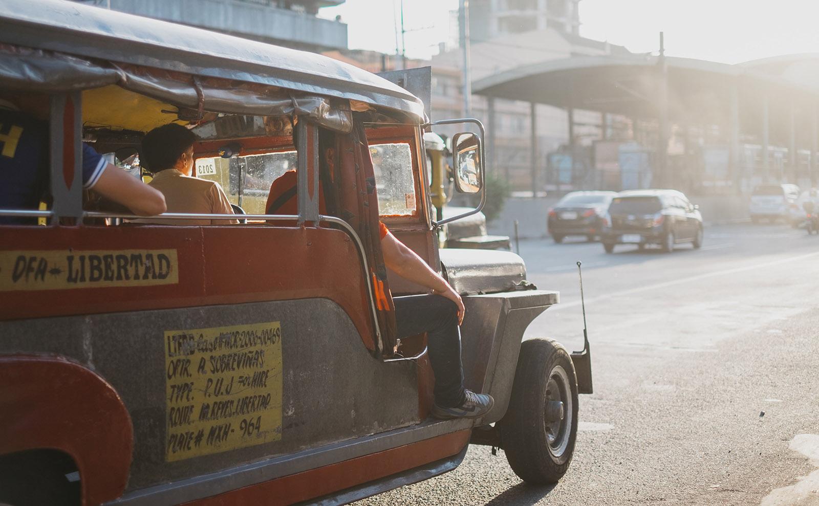 vintage car driving down manila street